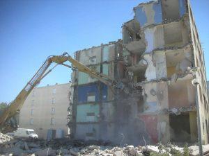 Démolition d'un immeuble de 5 étages avec pelle de démolition